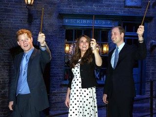 PHOTO: From left: Prince Harry, Kate the Duchess of Cambridge, and Prince William, raise their wands on the film set used to depict Diagon Alley in the Harry Potter Films during the inauguration of ...