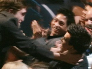 VIDEO: Robert Pattinson plants a kiss on co-star Taylor Lautner at MTV Movie Awards.
