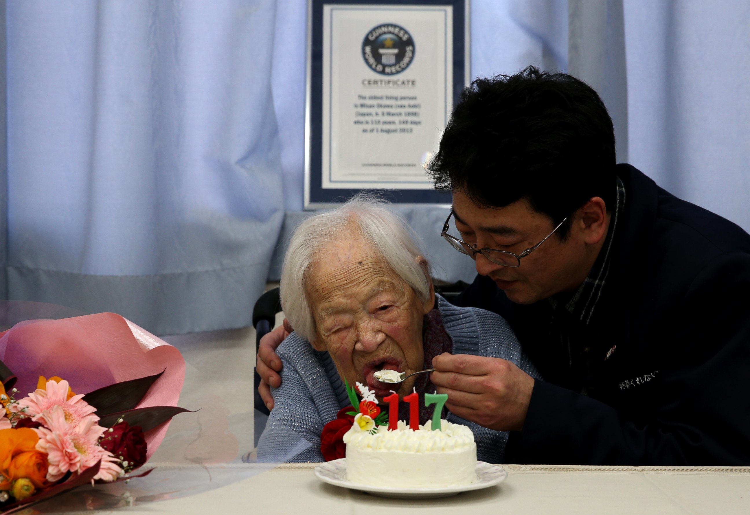 photo a nursing home employee helps misao okawa who is recognised by guinness world records as the worlds oldest living person eat her birthday cake on