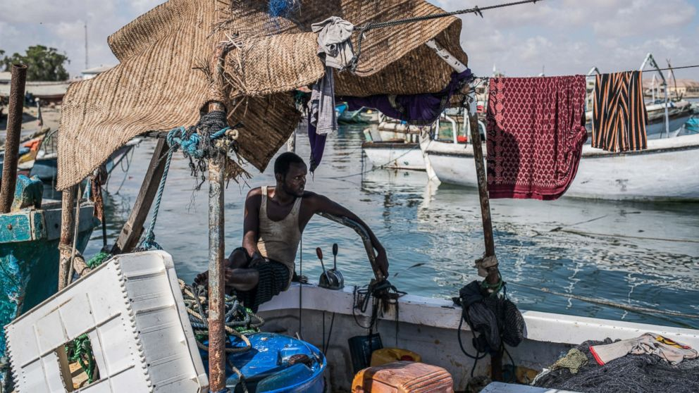 PHOTO: A fisherman relaxes in the shade of his boat, docked in the midday heat of Bosaso port in Somalia. From 2005 to 2012, piracy off Somalia posed the predominant threat to world shipping.