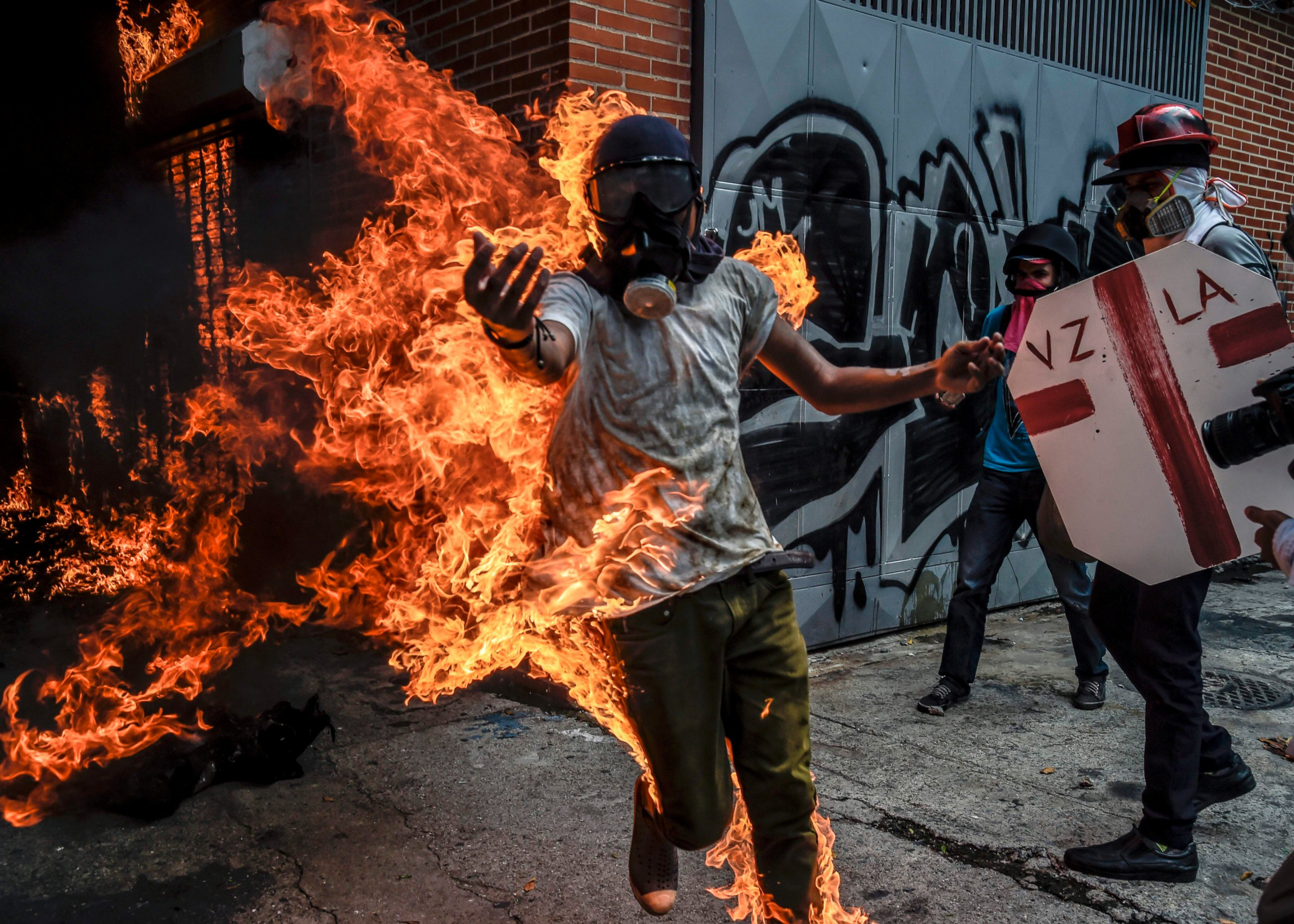 Image result for A demonstrator catches fire after the gas tank of a police motorbike exploded during clashes in a protest against Venezuelan President Nicolas Maduro, in Caracas, Venezuela, May 3, 2017.