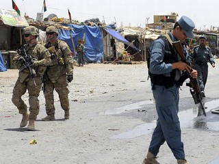 PHOTO: Afghan policemen stand guard as US soldiers arrive at the site of a twin suicide attack in a lot holding trucks supplying the NATO-run Kandahar Air Base, June 6, 2012.