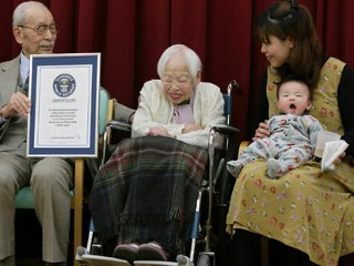 PHOTO: Japan's 114-year-old woman Misao Okawa smiles as she is recognized as the world's oldest woman by the Guinness World Record as her 90-year-old son Hiroshi, left, holds her framed certificate ...