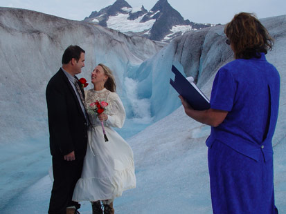 Bride and groom kiss amid the frozen glacier just outside of Juneau, Alaska. Temperatures on the glacier are usually only about 10-15 Fahrenheit degrees cooler than on land.