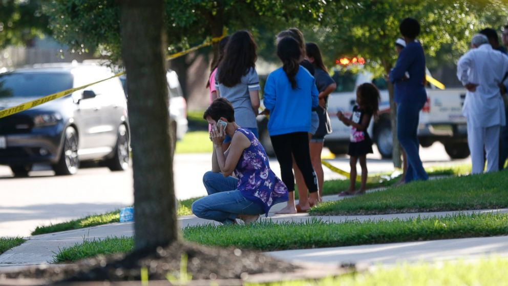 PHOTO: Neighbors gather to watch as Fort Bend County Sheriffs department investigates a scene where a woman shot her two adult daughters before she was fatally shot by a responding police officer, June 24, 2016.