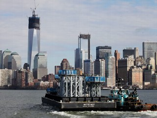 PHOTO: A barge loaded with sections of spire for One World Trade Center, left, is guided by tugboat across New York Harbor from New Jersey's Port Newark, Dec. 11, 2012 in New York.