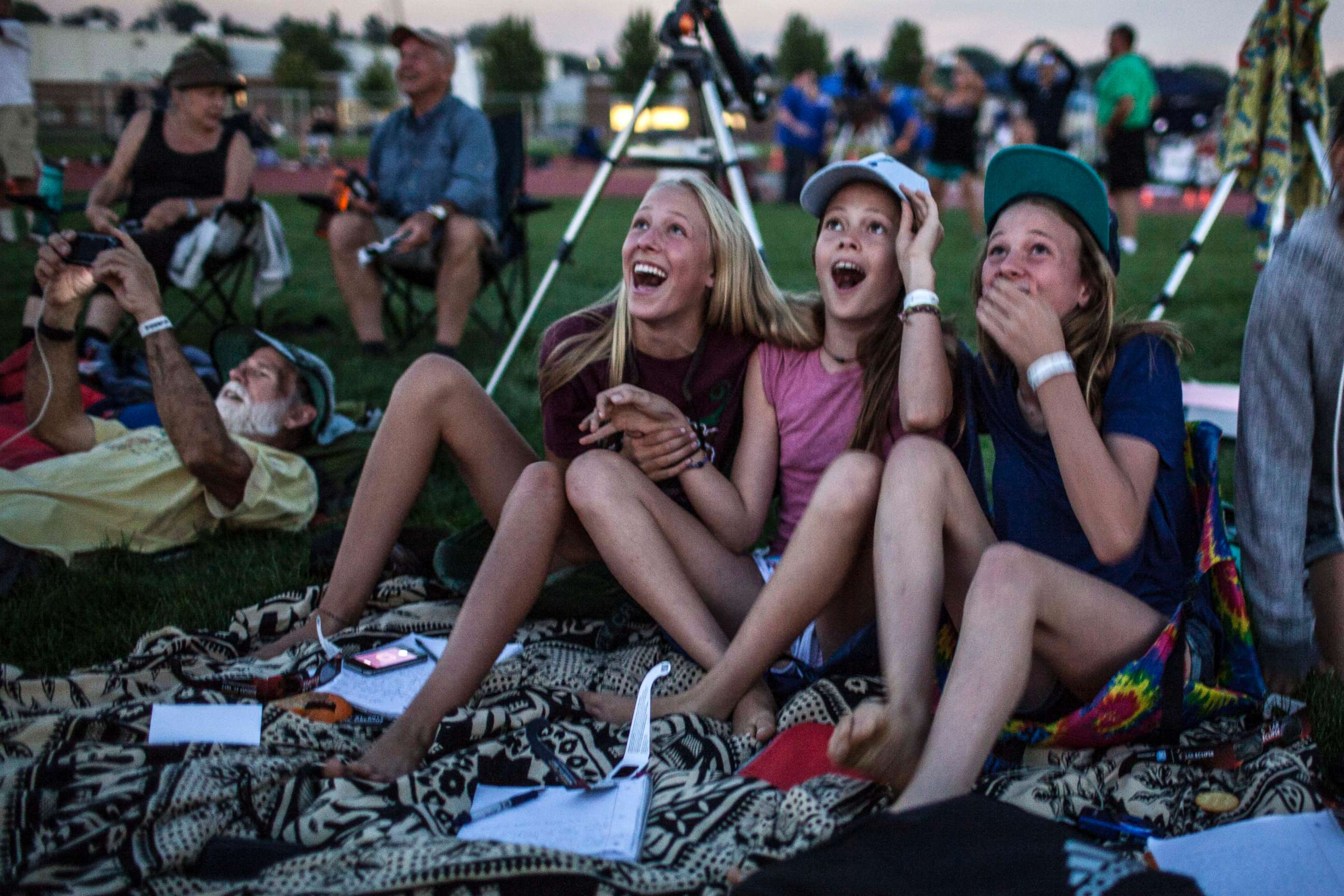 Image result for Autumn Stock, 12, Makaya Mackie, 12, and Lupin Amstutz, 13, from Yosemite Park High School react to the total solar eclipse in Madras, Oregon on Aug. 21, 2017.