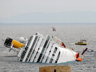 PHOTO: A rescue boat and an helicopter patrol near the Costa Concordia cruise ship on January 16, 2012.