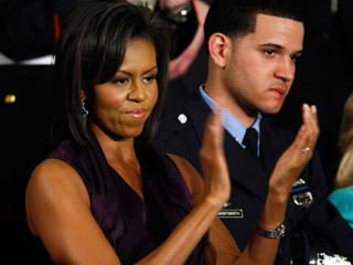 PHOTO: Michelle Obama applauds her husband, President Barack Obama, while he addresses a joint meeting of Congress as Philadelphia Police Officer Richard DeCoatsworth, right, stands by her, Feb. 24, ...
